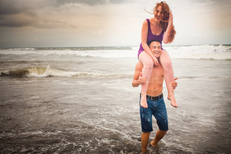 honeymooners: husband holding his wife on shoulders at the beach