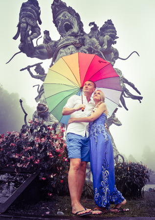 couple in rain: Couple travelling to Asia with umbrellas in bad weather, Balinese Botanical Garden