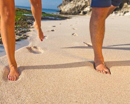 honeymooners: human legs running on the sandy beach Stock Photo