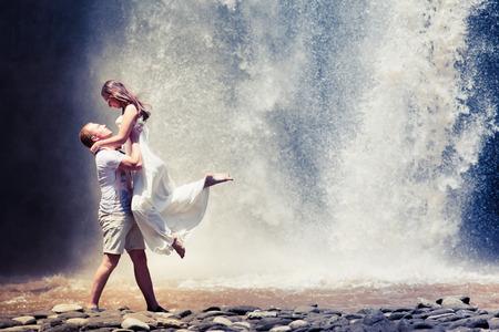 honeymooners: couple travel near the big waterfall Stock Photo