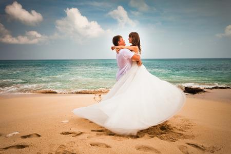 romance: casal de noivos recém-casados ??na praia