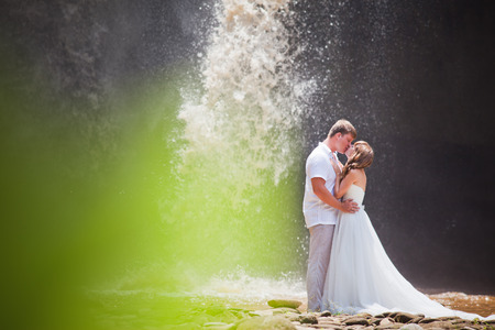 couple travel near the big waterfall, with green copy space photo