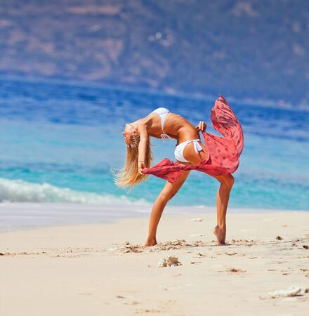 young girl dancing at the beach, summer vacation photo