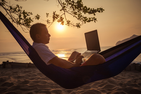 using a laptop: man uses laptop remotely at the beach