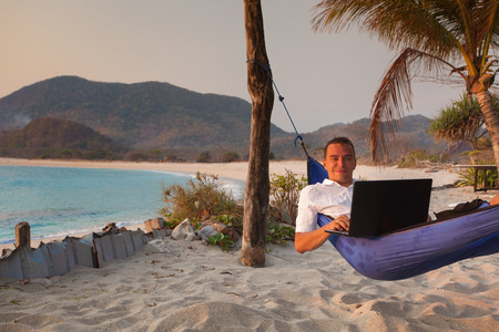 man uses laptop remotely at the beach