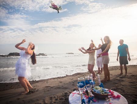 bridesmaids: Bride throwing bouquet for bridesmaids and groomsmen