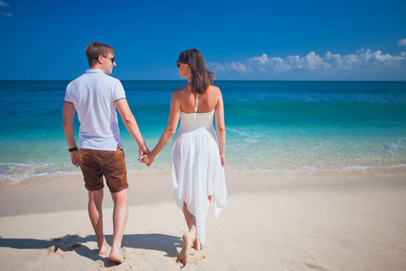 honeymooners: couple holding by hands walking on the white beach at Bali, Indonesia Stock Photo