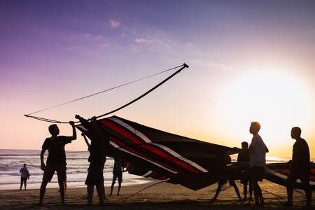 INDONESIA - AUGUST 17: Indonesian boys going to fly a kite near the coast on the background of clear sky  AUGUST 17, 2014. INDONESIA. During the Indonesian holidays, there are competitions of flying kite, this is a national traditions
