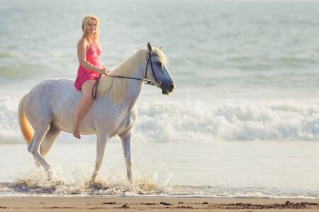 Beautiful young woman riding a horse along the beach, she is happy of her hobby Stock Photo
