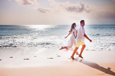 honeymooners: honeymooners couple jogging on the beach Stock Photo