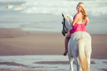 horse blonde: Beautiful young woman riding a horse along the beach, she is happy of her hobby Stock Photo