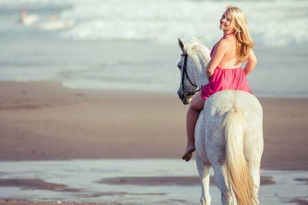 femme a cheval: Belle jeune femme sur un cheval le long de la plage, elle est heureuse de son passe-temps Banque d'images