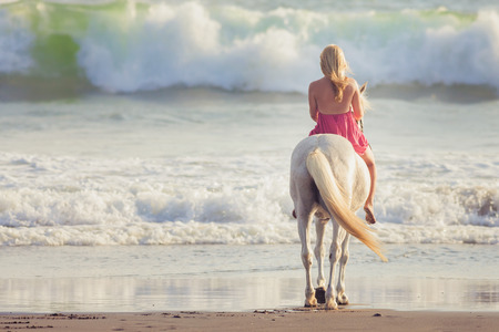 woman and horse: Beautiful young woman riding a horse along the beach
