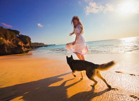 personas trotando: mujer que viaja con el perro cerca de la playa