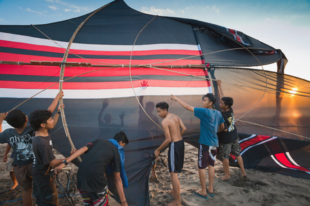 INDONESIA AUGUST 17: Indonesian boys going to fly a kite near the coast on the background of clear sky AUGUST 17 2014. INDONESIA. During the Indonesian holidays there are competitions of flying kite this is a national traditions