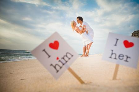 novios besandose: marco blanco del concepto de amor con el texto y el coraz�n rojo, hay una pareja bes�ndose vestido de blanco en el fondo Foto de archivo