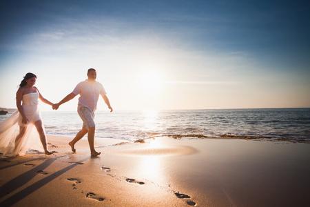 honeymooners: honeymooners happy couple dressed in white running or jogging on the beach