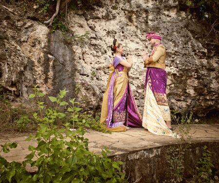 honeymooners: Vintage image of wedding ceremony of mature couple dressed in Balinese costume