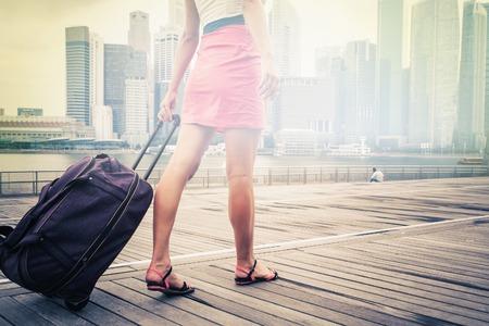 mujer con maleta: aventura tur�stica o una mujer con el equipaje en Singapur en frente de los edificios comerciales y oficinas, hay un punto brillante en el centro de cualquier texto