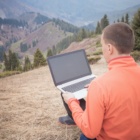 3g: man dressed in red sweater uses laptop remotely with 3g or 4g network wireless at mountain, square orientation