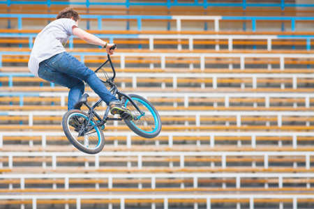 tribune: Image of teenager on a bicycle in a high jump on a background tribune of stadium Stock Photo