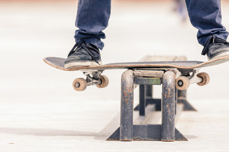 close-up image of teenager doing a trick by skateboard on a rail in the skate park outdoors