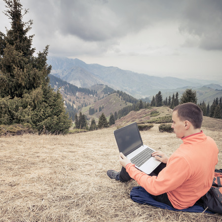 communication concept: man dressed in red sweater uses laptop remotely with 3g or 4g network wireless at mountain, square orientation