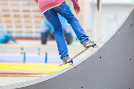 kicker: close-up image of teenager doing a trick by skateboard on a kicker in the skate park outdoors, focus at the foreground on a kicker Stock Photo