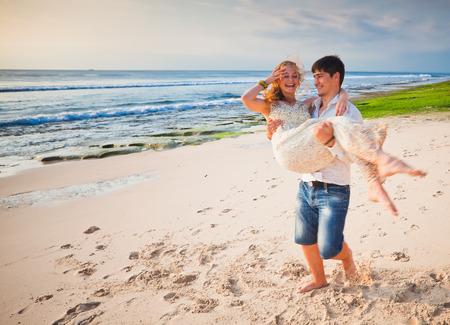 honeymooners: los reci�n casados ??felices pareja en la playa de Bali. Individuo que sostiene a su novia por las manos, y ella riendo con alegr�a Foto de archivo