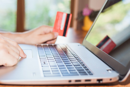 e commerce: Concept of online payment by plastic card through the Internet Banking. Close-up of human hand for laptop and holding credit card, man is shopping indoor at home