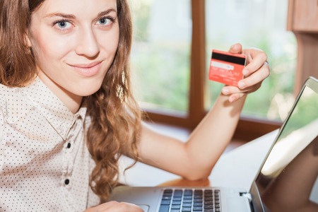 Beautiful successful woman holding credit card, and shopping through laptop. Concept of fast and reliable online payment by plastic card through the Internet Banking. photo