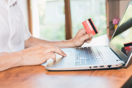 online purchase: Concept of online payment by plastic card through the Internet Banking. Close-up of human hand for laptop and holding credit card, man is shopping indoor at home