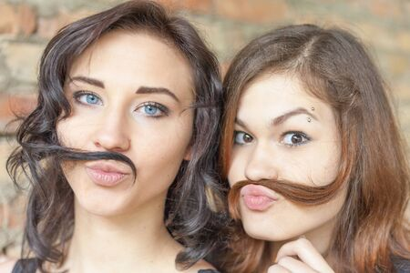 adult person: Two young pretty girls making mustache of their hair. They are now a party or birthday, and celebrate fun!