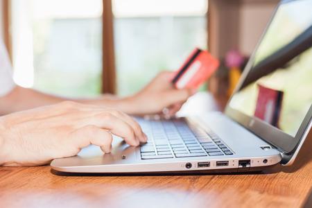 Konzept der Online-Zahlung über Plastikkarte über das Internet Banking. Close-up der menschlichen Hand für Laptop und mit Kreditkarte, wird Mann Einkaufen Innen zu Hause Standard-Bild - 40708148