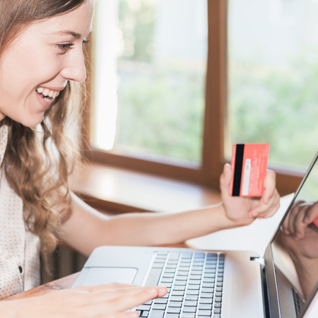 e pretty: Beautiful surprised and successful woman holding credit card, and make online payment by plastic card through Internet Banking. She saw a lot of money on account, or something interesting on Internet. Stock Photo