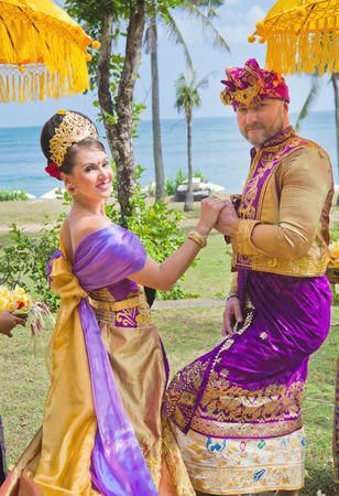 honeymooners: Wedding ceremony of mature beautiful couple dressed in Balinese costume near the beach and blue sea