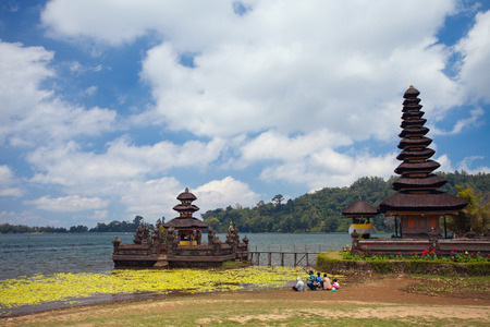bratan: Image of the main water temple Ulun Danau Bali on Bratan Lake, close to the shore like a small house with a roof at 11 storeys. Front of the temple family of five sitting and go fishing together. Indonesia. Stock Photo