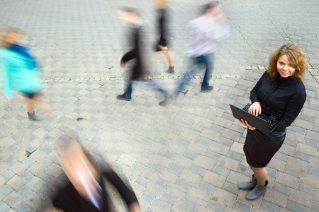 wireless technology: Young attractive businesswoman working on laptop through wireless technology. Motion blurred commuters walking to work