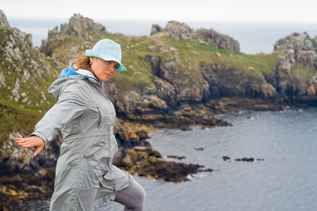 resisting: Picture of a girl, resisting strong winds at the edge of the world - Finister in France. Stock Photo