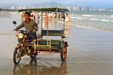 observers: Image of rickshaw driver looking for new clients on the beach, group of Hainan fishers gathering the net on the beach and casual observers looking after the catch on the background. One young women is taking of photograph.