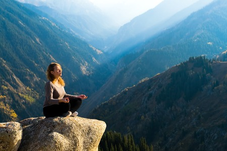 inspiration: Yoga at summit with aerial view of the mountain range and peak. Blue sky.