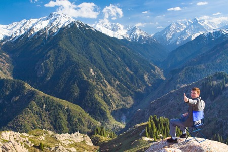 successes: Image of a young businessman who sits on a chair at the top of the mountain and looks at the camera on the background of the beautiful mountains, pleased with the achieved successes.