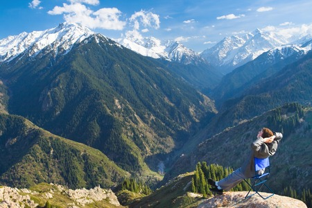 successes: Image of a young businessman who sits on a chair at the top of the mountain on the background of the beautiful mountains, relaxing and pleased with the achieved successes. Stock Photo