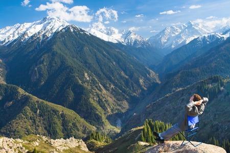 successes: Immagine di un giovane uomo d'affari che si siede su una sedia in cima alla montagna sullo sfondo di splendide montagne, rilassante e soddisfatti dei successi ottenuti.