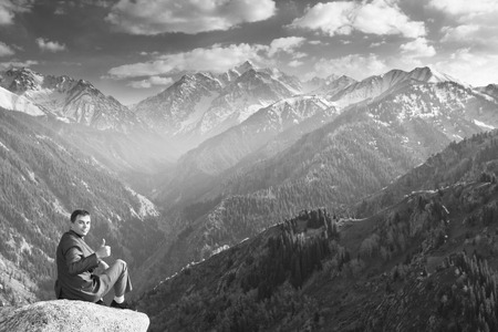 successes: Black and white Image of a young businessman who sits on the top of the mountain and looks at the camera on the background of the beautiful mountains, pleased with the achieved successes.