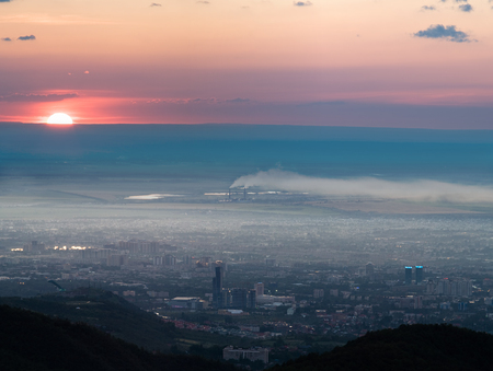Panorama image of pollution city of Almaty, Kazakhstan, Asia. Mountain aerial view image of sun at sunset cloudscape Stock Photo