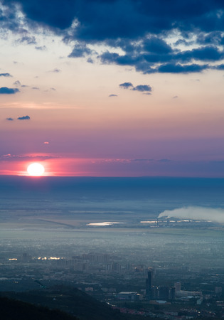 particulate: Panorama image of pollution city of Almaty, Kazakhstan, Asia. Mountain aerial view image of sun at sunset cloudscape Stock Photo