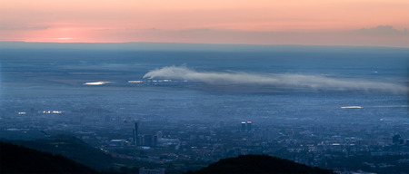 ozone layer: Panorama image of pollution city of Almaty, Kazakhstan, Asia. Mountain aerial view image of sun at sunset cloudscape Stock Photo