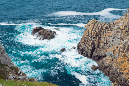 harsh: Picture harsh landscape - the beating of waves on the high cliffs at a height of several tens of meters from the place of photography. Stock Photo