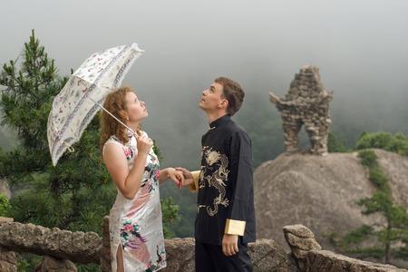 uomo sotto la pioggia: Immagine Ritratto di bella coppia con l'ombrello al tempo nuvoloso in cima alla montagna cinese di Huangshan (montagna gialla). Indossare vestiti cinesi. Cina, Asia. Archivio Fotografico